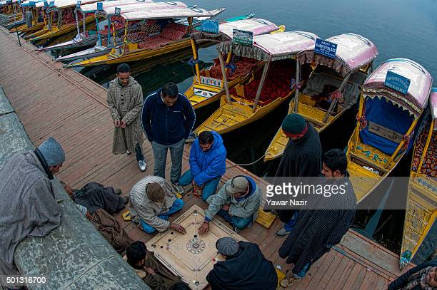 Boatmen play a carom game on a dock where boats are moored to the bank of Dal Lake on December 14 2015 in Srinagar the summer capital of Indian...