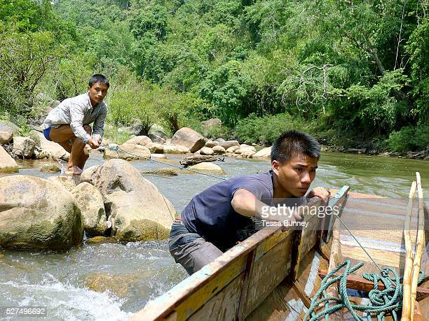 Boatmen Sengkham and Savath pull their boat up the rapids on the Nam Ou river using a rope during the dry season when the river level is low...