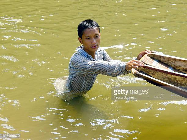 Boatmen Sengkham rests after pushing the boat up the rapids on the Nam Ou river during the dry season when the river level is low Phongsaly province...