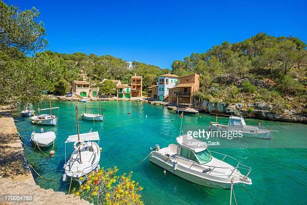 Barche e case Majorcian nella baia di Cala Figuera