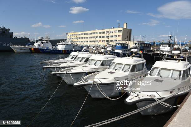 Boats and ships of the Romanian border police are pictured in Constanta southeastern Romania on September 13 2017 Families of migrants landing on...