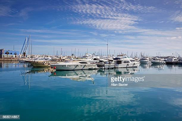 Boats and yachts in Alicante harbour with blue sky