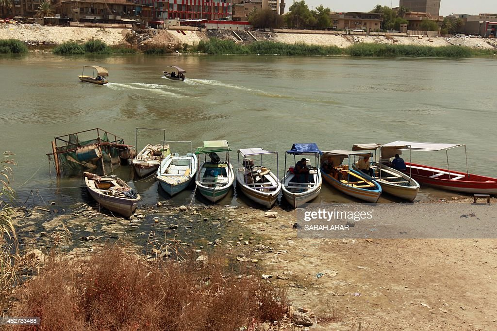 Boats are seen docked on the bank of the Tigris River that runs through the center of the Iraqi Capital Baghdad on August 2 2015 AFP PHOTO / SABAH...