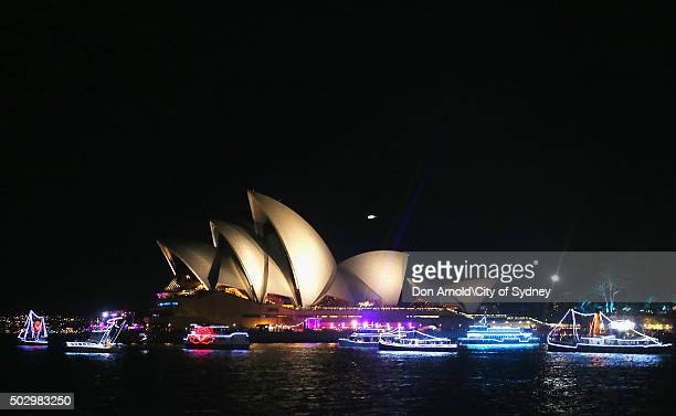 Boats are seen illuminated against an Opera House backdrop on New Year's Eve on Sydney Harbour on January 1 2016 in Sydney Australia