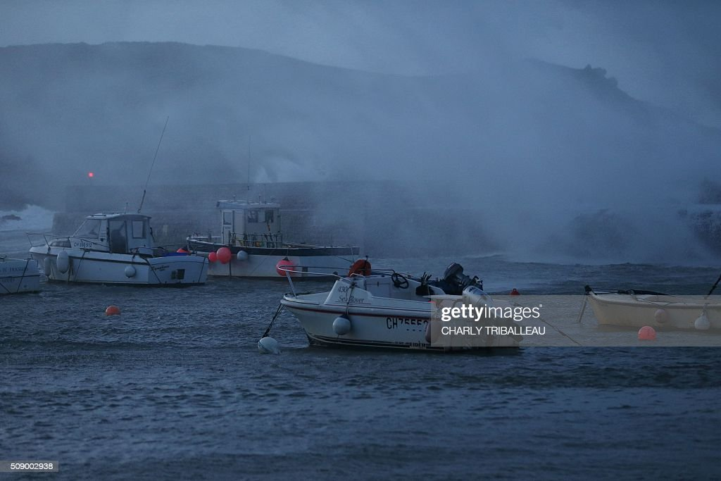 Boats are seen in the harbour in Auderville, northwestern France, on February 8, 2016, as strong winds hit the region. Winds of over 130 kh/h were recorded in the region where 16 departments have been placed under alert for wind and flooding waves. / AFP / CHARLY TRIBALLEAU
