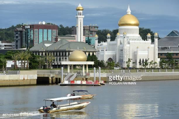 Boats are seen past Brunei's Sultan Omar Ali Saifuddin mosque in Bandar Seri Begawan on October 4 2017 Brunei will mark its Sultan's Hassanal Bolkiah...