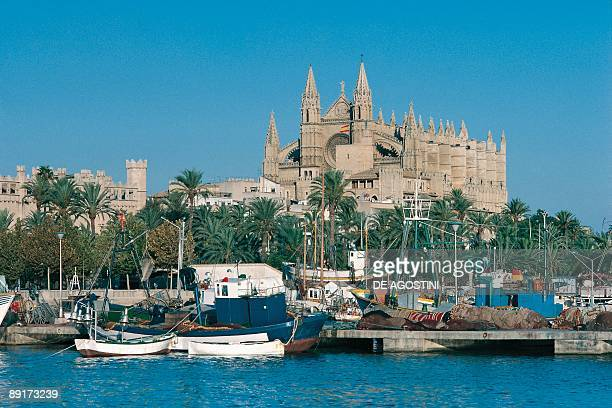 Boats at a harbor with a cathedral in the background Palma Cathedral Palma Majorca Balearic Islands Spain