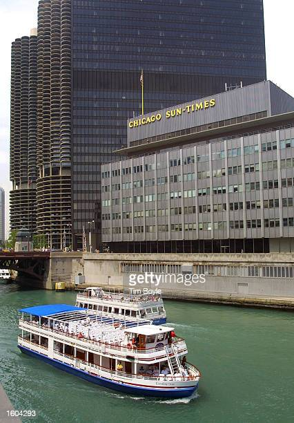 Boats cruise along the Chicago River July 25 2001 in front of the Chicago SunTimes building in downtown Chicago Donald Trump and the owners of the...