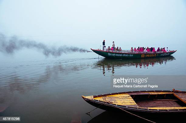 Boats full of indian tourists or pilgrims sailing on the Ganges river in a misty morning