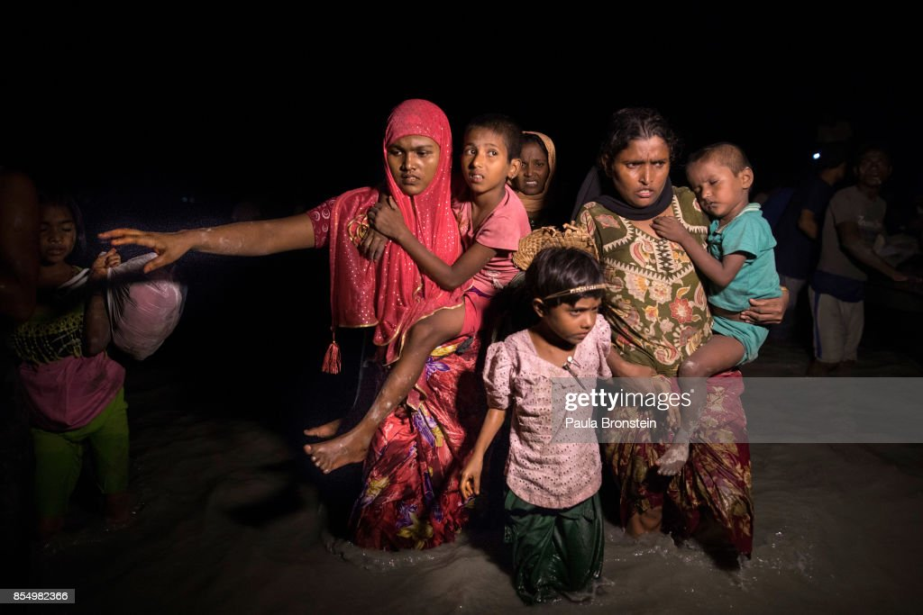 Boats full of people continue to arrive along the shores of the Naf river as Rohingya refugees arrive in the safety of darkness September 27, 2017 on Shah Porir Dwip island, Cox's Bazar, Bangladesh. Over 480,000 Rohingya refugees have fled into Bangladesh since late August during the outbreak of violence in Rakhine state as Myanmar's de facto leader Aung San Suu Kyi downplayed the crisis during a speech in Myanmar this week faces and defended the security forces while criticism on her handling of the Rohingya crisis grows. Bangladesh's prime minister, Sheikh Hasina, spoke at the United Nations General Assembly last week, focusing on the humanitarian challenges of hosting the minority Muslim group who currently lack food, medical services, and toilets, while new satellite images from Myanmar's Rakhine state continue to show smoke rising from Rohingya villages.