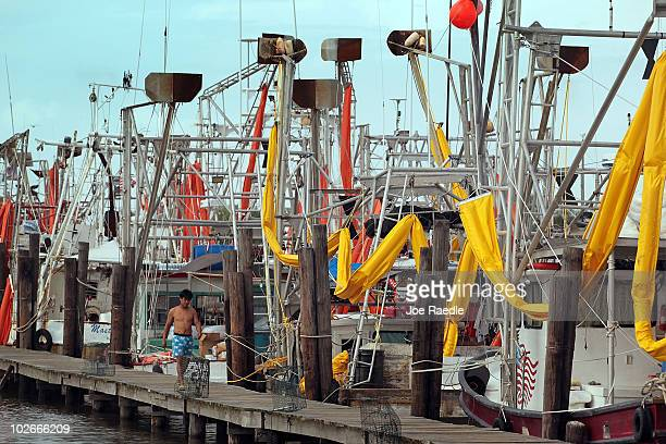Boats hired by BP to help with oil skimming sit at port with their oil containment booms hung from their riggings after being forced in due to rough...