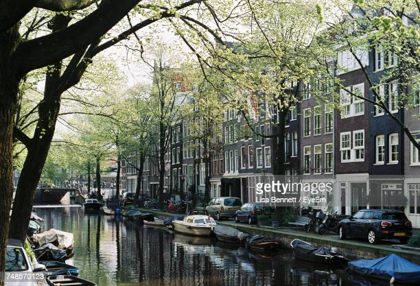 Boats In Amstel River Canal Amidst Cars And Buildings In City