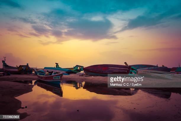Boats In Calm Lake At Sunset