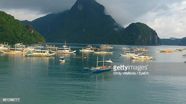 Boats In Calm Sea Against Mountain Range