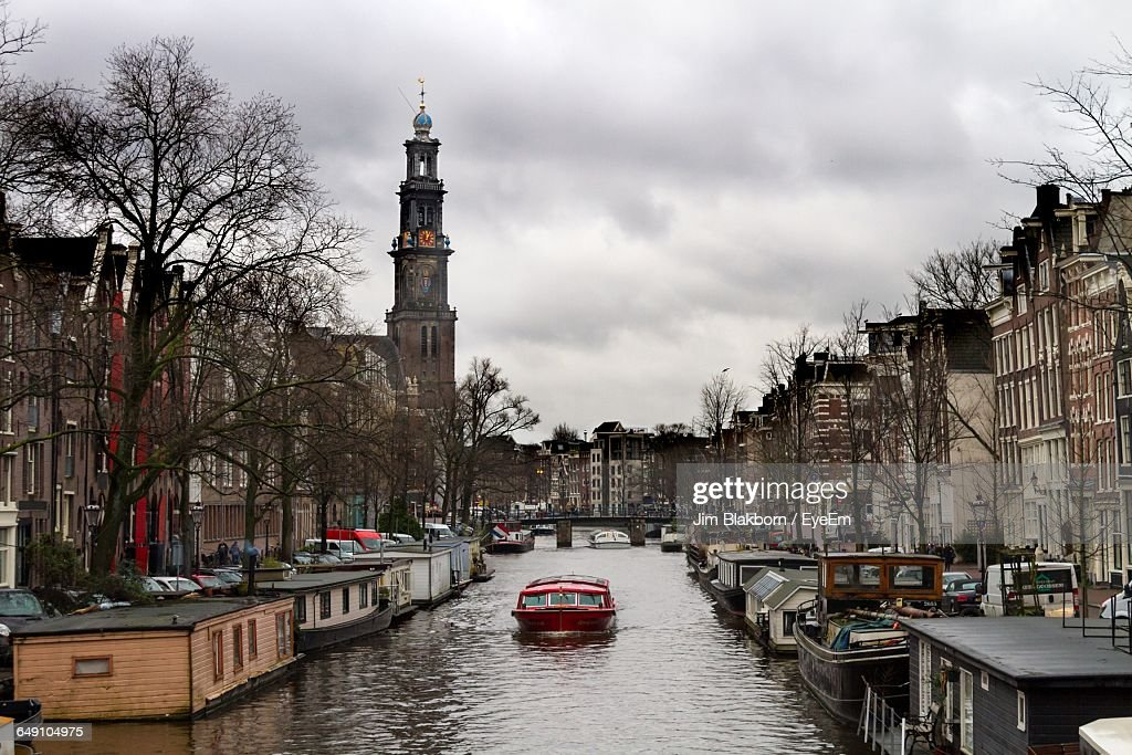 Boats In Canal Amidst Buildings Against Sky