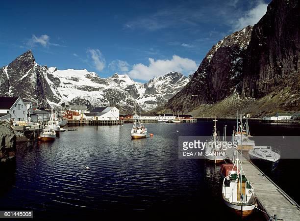 Boats in Sakrisoya harbour with the summits of the Lofotenveggen in the background Moskenesoya island Lofoten islands Nordland Norway