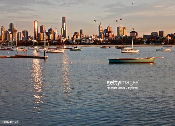 Boats Moored At Harbor By Cityscape Against Sky