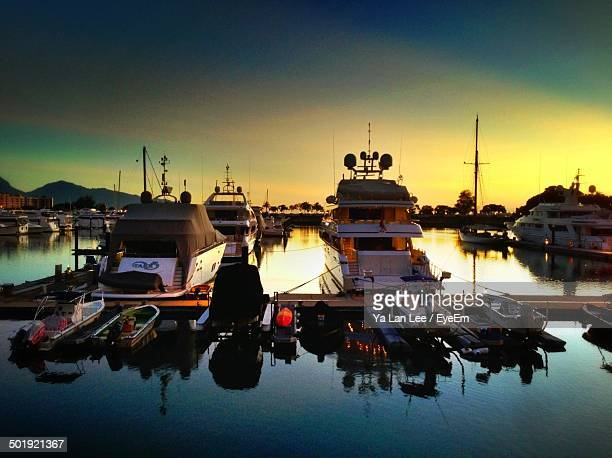 Boats moored at harbor during dusk