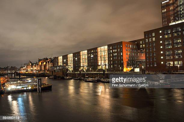 Boats Moored At Illuminated Harbor Against Cloudy Sky At Night