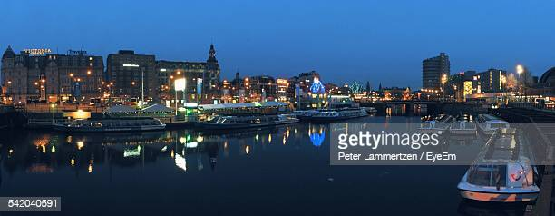 Boats Moored At Lake And Illuminated Cityscape Against Clear Sky At Dusk