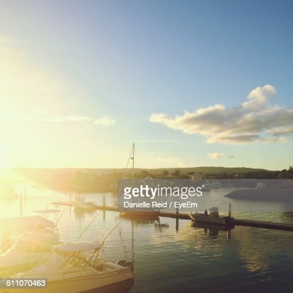 Boats moored in calm sea against the sky