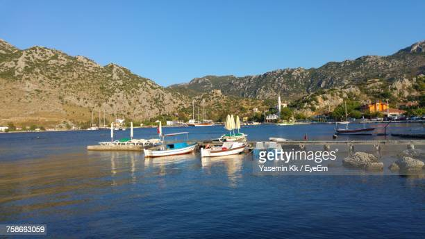 Boats Moored In Lake Against Clear Blue Sky