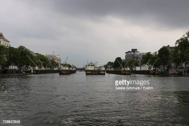Boats Moored In River Against Sky In City