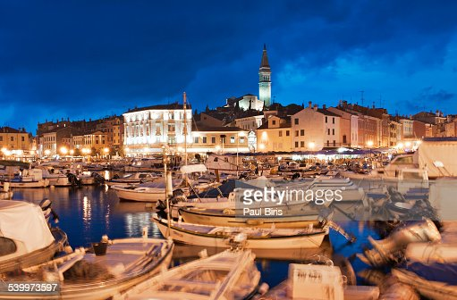 Boats moored in Rovinj old town harbor at night