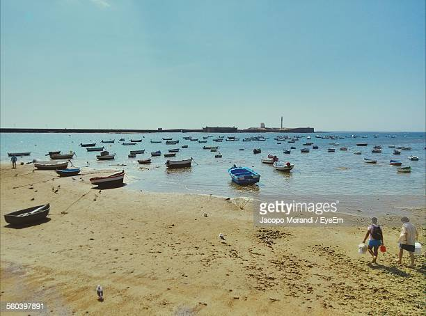 Boats Moored On Beach Against Clear Sky