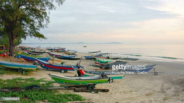 Boats Moored On Beach Against Sky