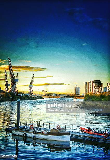 Boats Moored On River By Cranes And Cityscape Against Sky