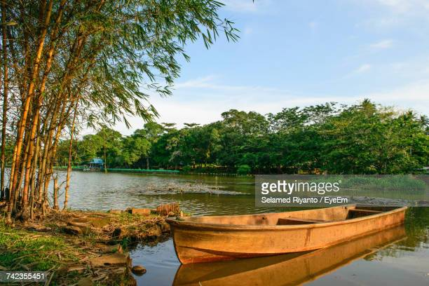 Boats Moored On River By Trees