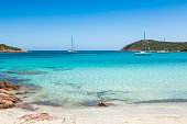 Boats mooring in the turquoise water of  Rondinara beach in Corsica Island in France