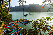 Colorful canoe boats at sunrise on Phewa Lake in Pokhara, Nepal.