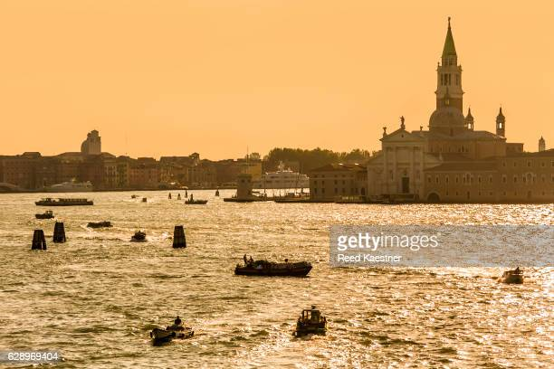 Boats on the Grand Canal during a golden sunset in Venice, Italy