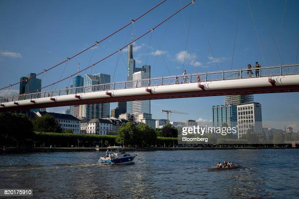 Boats pass underneath a bridge spanning the River Maine as skyscrapers stand beyond in Frankfurt Germany on Thursday July 20 2017 Frankfurt has...