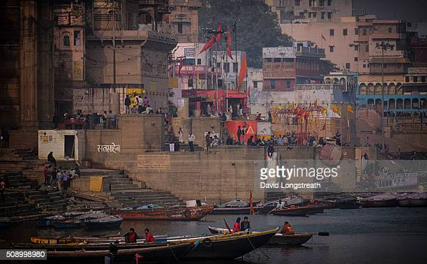 Boats ride on the Ganges river near a bathing ghat