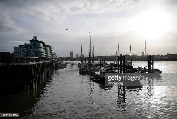 Boats sit moored at berths on a floating pontoon over the River Thames close to the former News International newspaper site in Wapping London UK on...