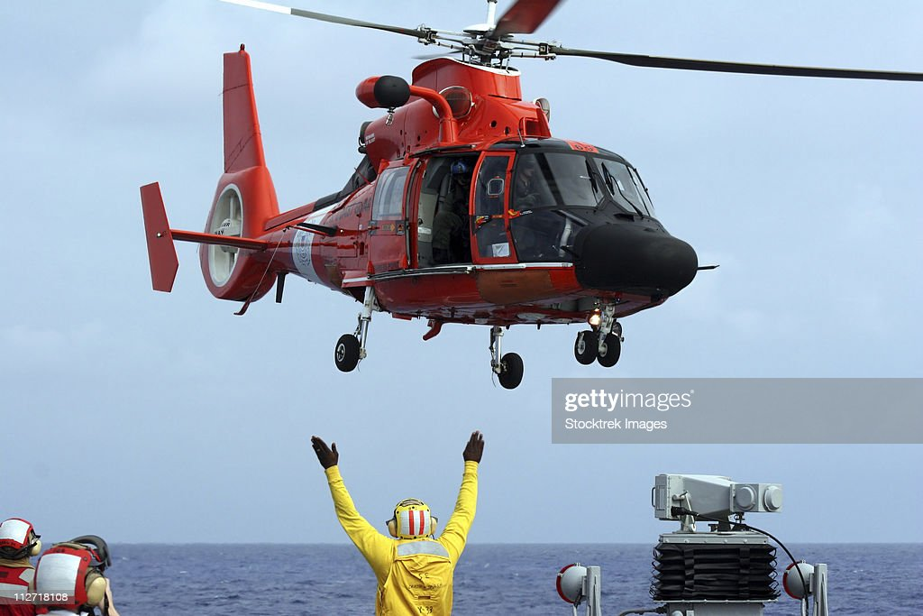 Boatswain Mate directs a HH-65A Dolphin aboard the guided-missile destroyer USS Russell.