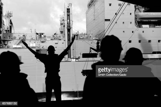 Boatswain's Mate 1st Class Stephen Markman assigned to the aircraft carrier USS George H W Bush signals to personnel abroad the Military Sealift...