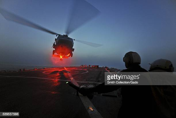 Boatswain's Mate 2nd Class Leon Simmons assigned to the guidedmissile destroyer USS Porter DDG 78 signals to an SH60B Sea Hawk helicopter during...