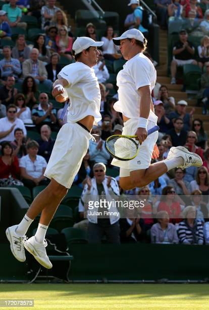 Bob and Mike Bryan bump chests as they celebrate match point during their Gentlemen's Doubles third round match against Treat Huey of Philippines and...