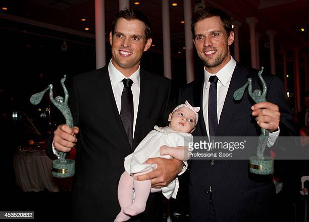 Bob and Mike Bryan of USA pose with Bob's baby daughter Micaela after receiving their Men's Doubles World Champion awards during the ITF World...