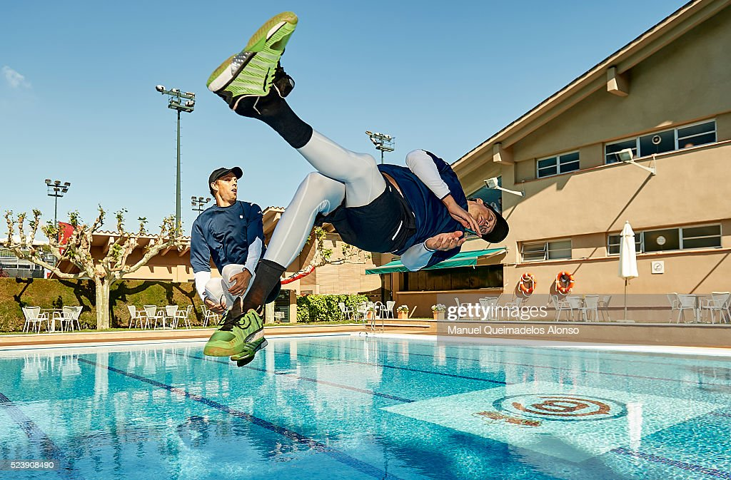 Bob Bryan and Mike Bryan of the United States dive in the swimming pool after defeating Marcel Granollers of Spain and Pablo Cuevas of Uruguay in the...