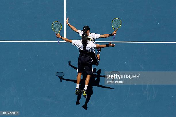 Bob Bryan and Mike Bryan of the United States of America chest bump in celebration of winning their doubles semifinal match against Horia Tecau of...