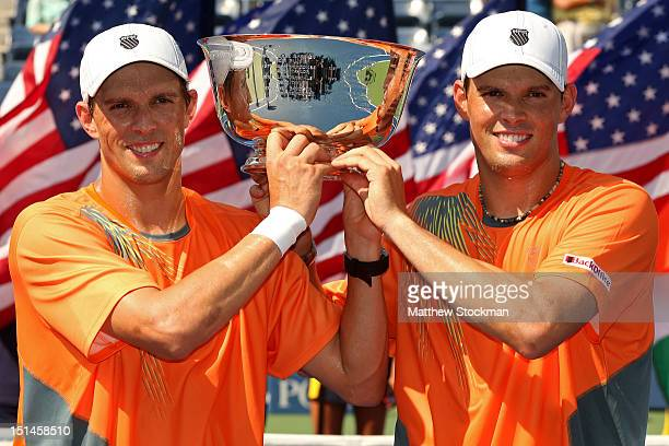 Bob Bryan and Mike Bryan of the United States pose with the trophy after their men's doubles final match against Leander Paes of India and Radek...