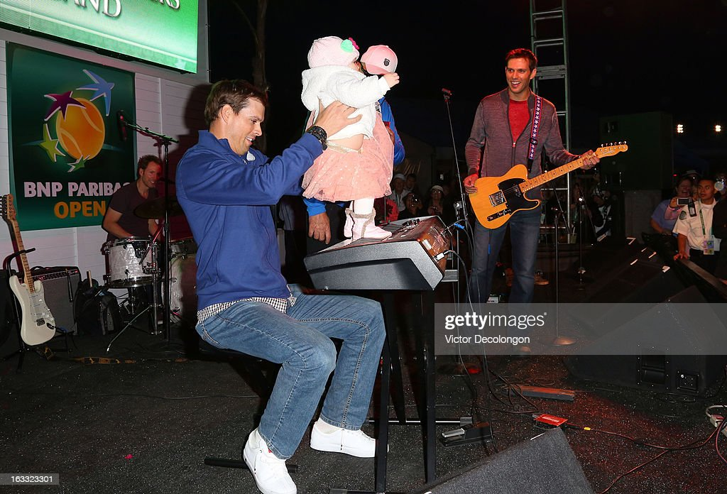 Bob Bryan helps his daughter Micaela play the keyboard onstage as brother Mike Bryan looks on during a concert at Indian Wells Tennis Garden on March 7, 2013 in Indian Wells, California.