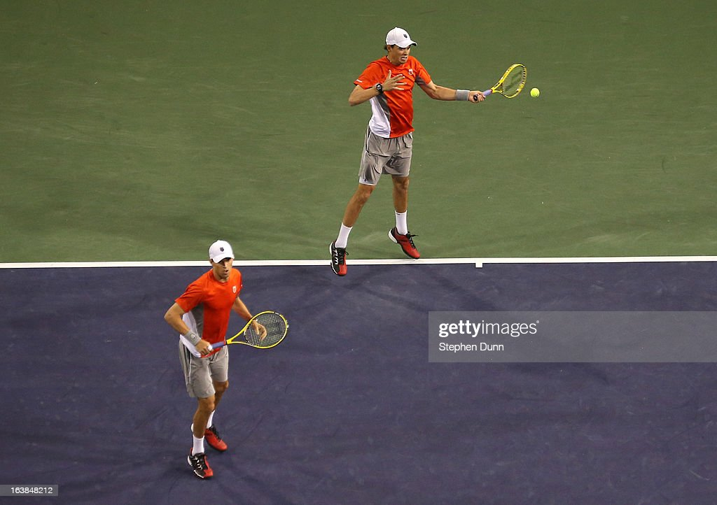 Bob Bryan hits a return past Mike Bryan to Treat Huey of the Philippines and Jerzy Janowicz of Poland during the men's doubles final during day 11 of the BNP Paribas Open at Indian Wells Tennis Garden on March 16, 2013 in Indian Wells, California.