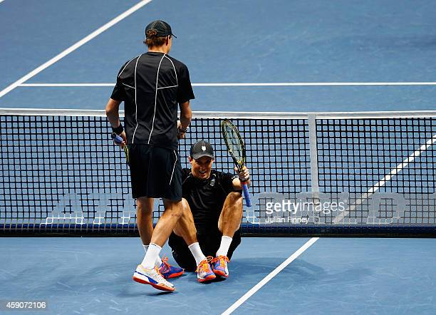 Bob Bryan of the United States helps Mike Bryan of the United States to his feet after he hit him on the head with his serve in the doubles final...