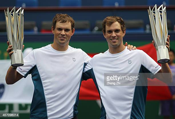 Bob Bryan of USA and Mike Bryan of USA victorious with trophies after winning their doubles final match against Julien Benneteau of France and...